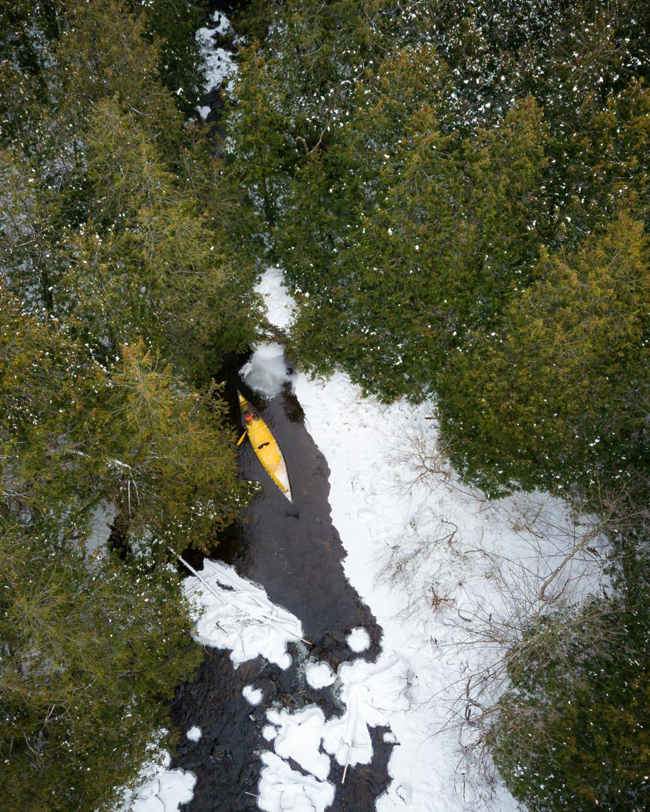 Aerial view of person paddling kayak through Eramosa river and Rockwood forest in winter