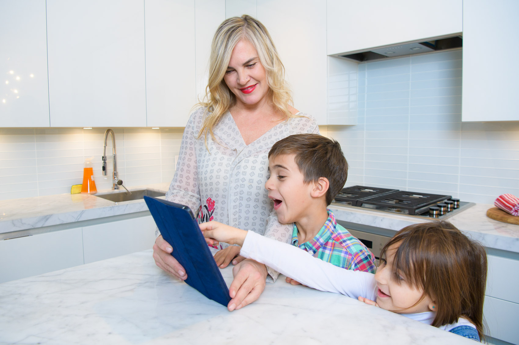 A mom holds an ipad with two children pointing at it in a kitchen