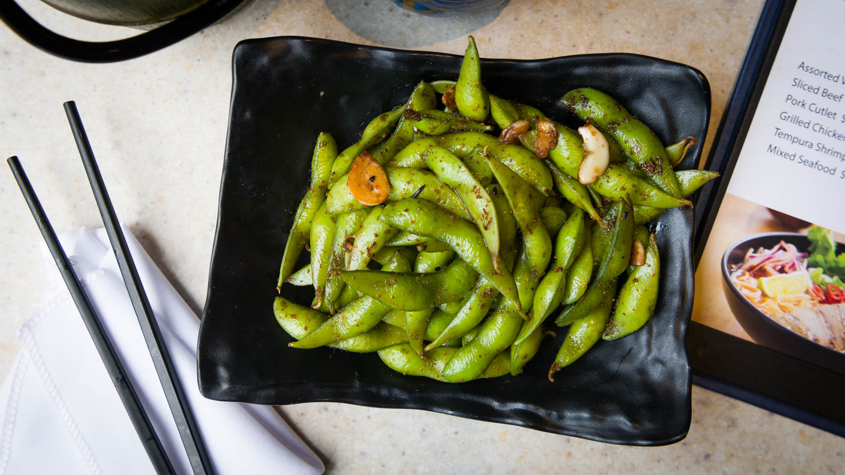 A plate of edamame with chopsticks and a menu at Pokerrito