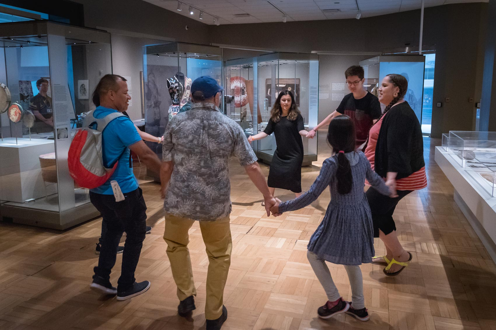 A group of people holding hands in a circle dancing at the Royal Ontario Museum