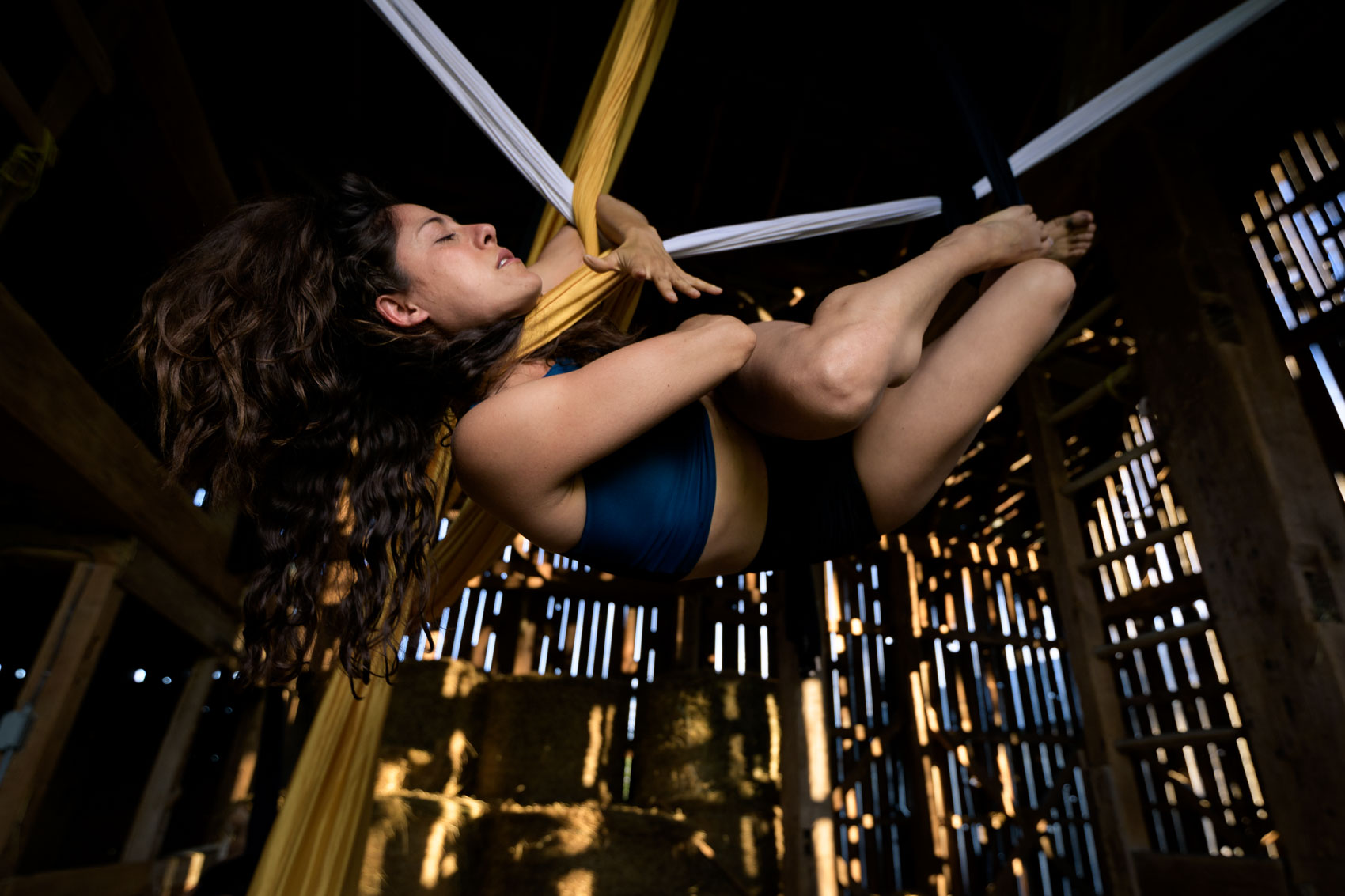 An aerial silk dancer hangs from silk in a barn