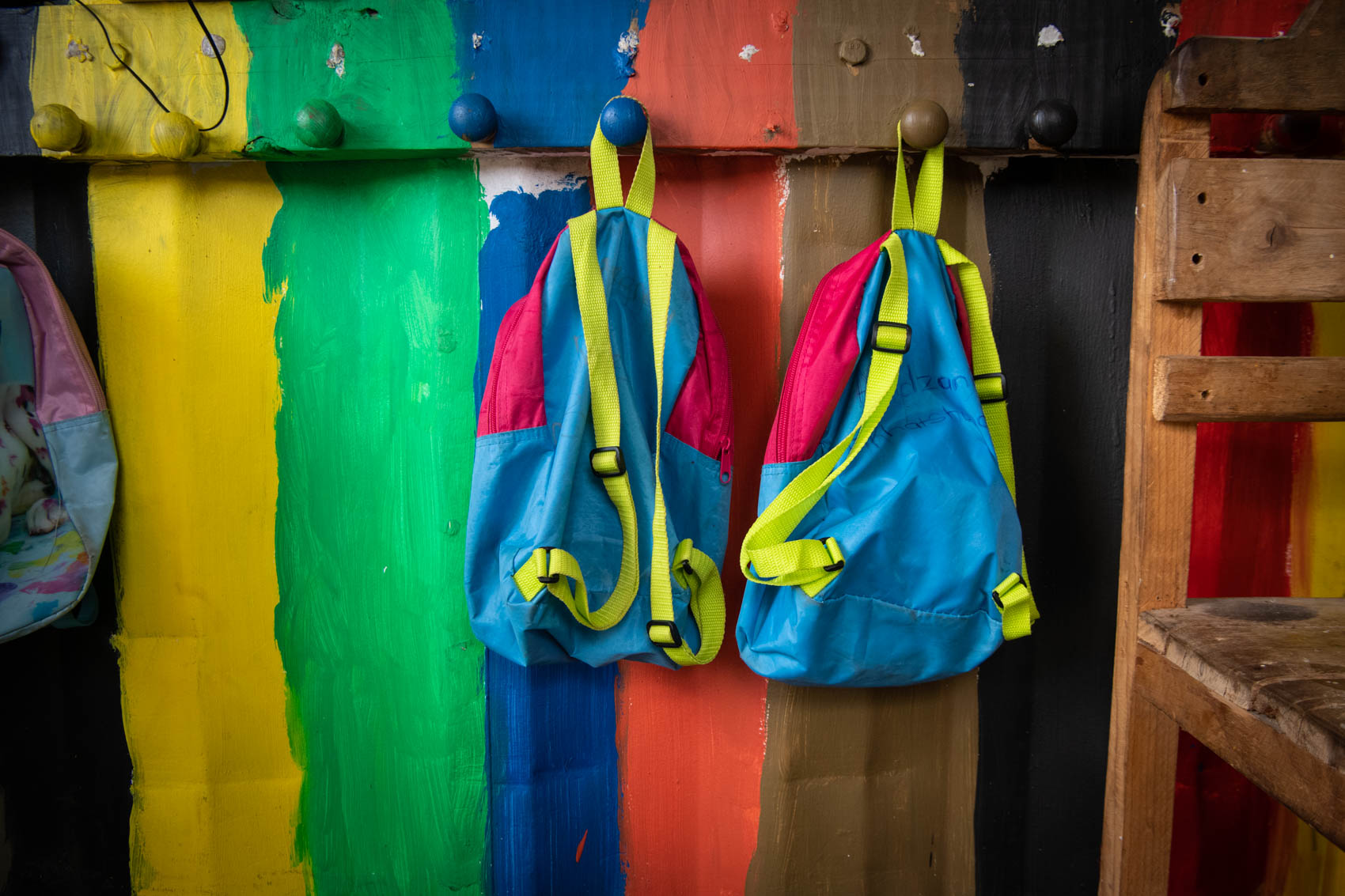 Two children backpacks hanging against a colourful wooden wall