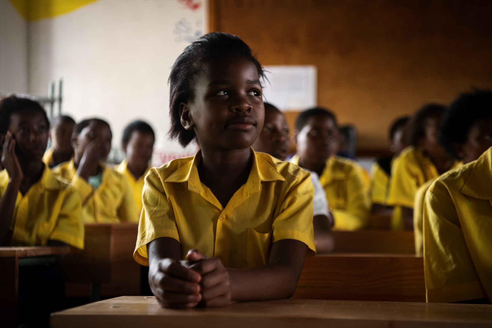 An African school girl in uniform looks on with classmates behind her in South Africa