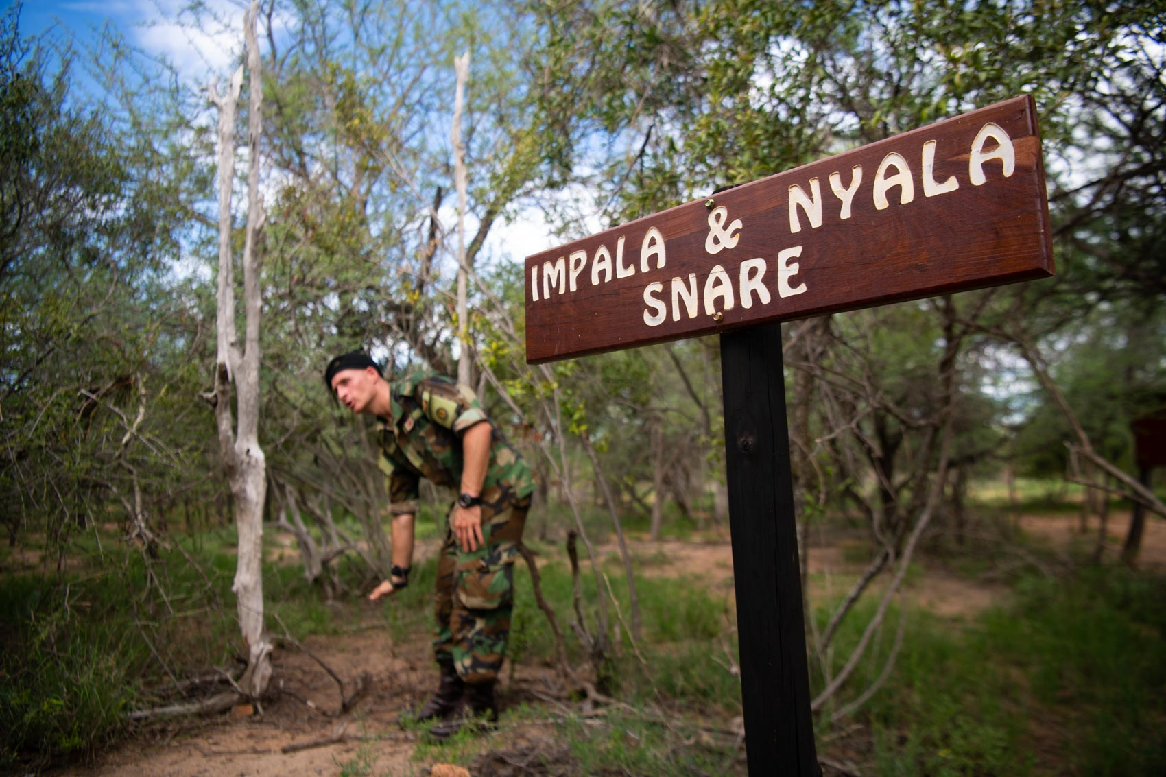 "A sign reads ""Impala & Nayla snare"" with a Protrack Anti-Poaching Unit instructor pointing behind it"