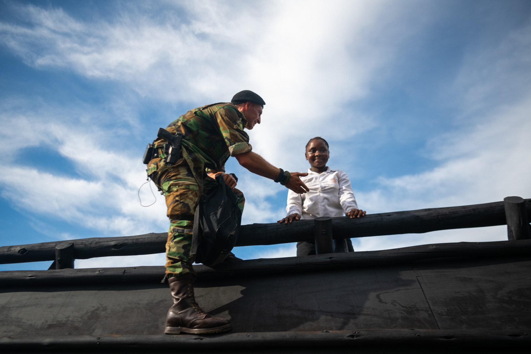 A Protrack Anti-Poaching Unit instructor helping a school girl over an obstacle