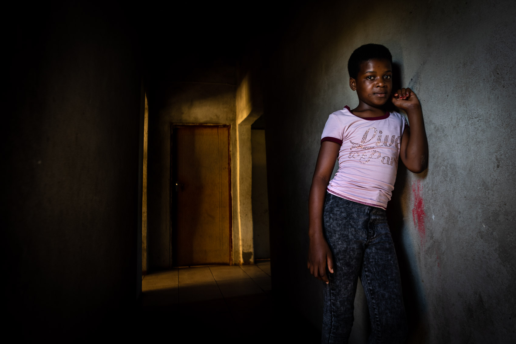 An African girl leaning on a wall inside a house in South Africa