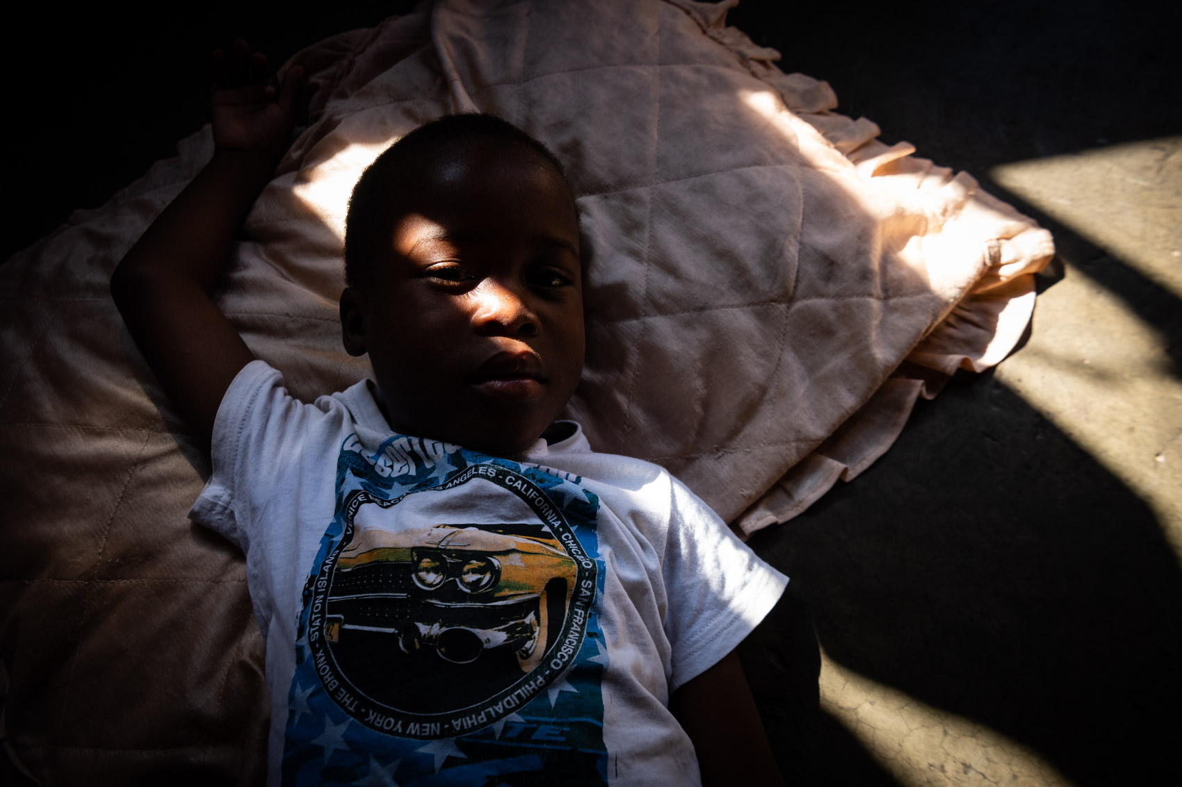 An African boy laying on the ground with a pillow with a ray of light across boy's face