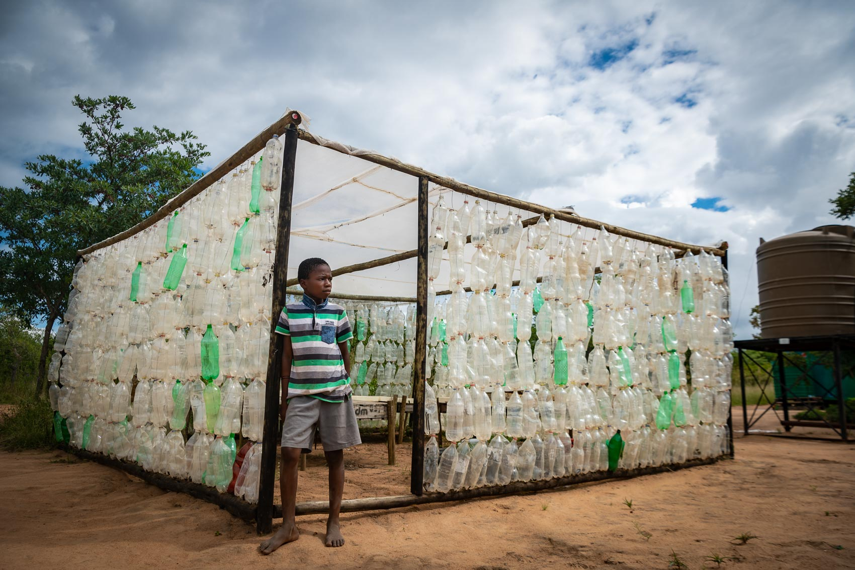 An African boy leaning against a wooden structure made from recycled bottles at Nourish NPO
