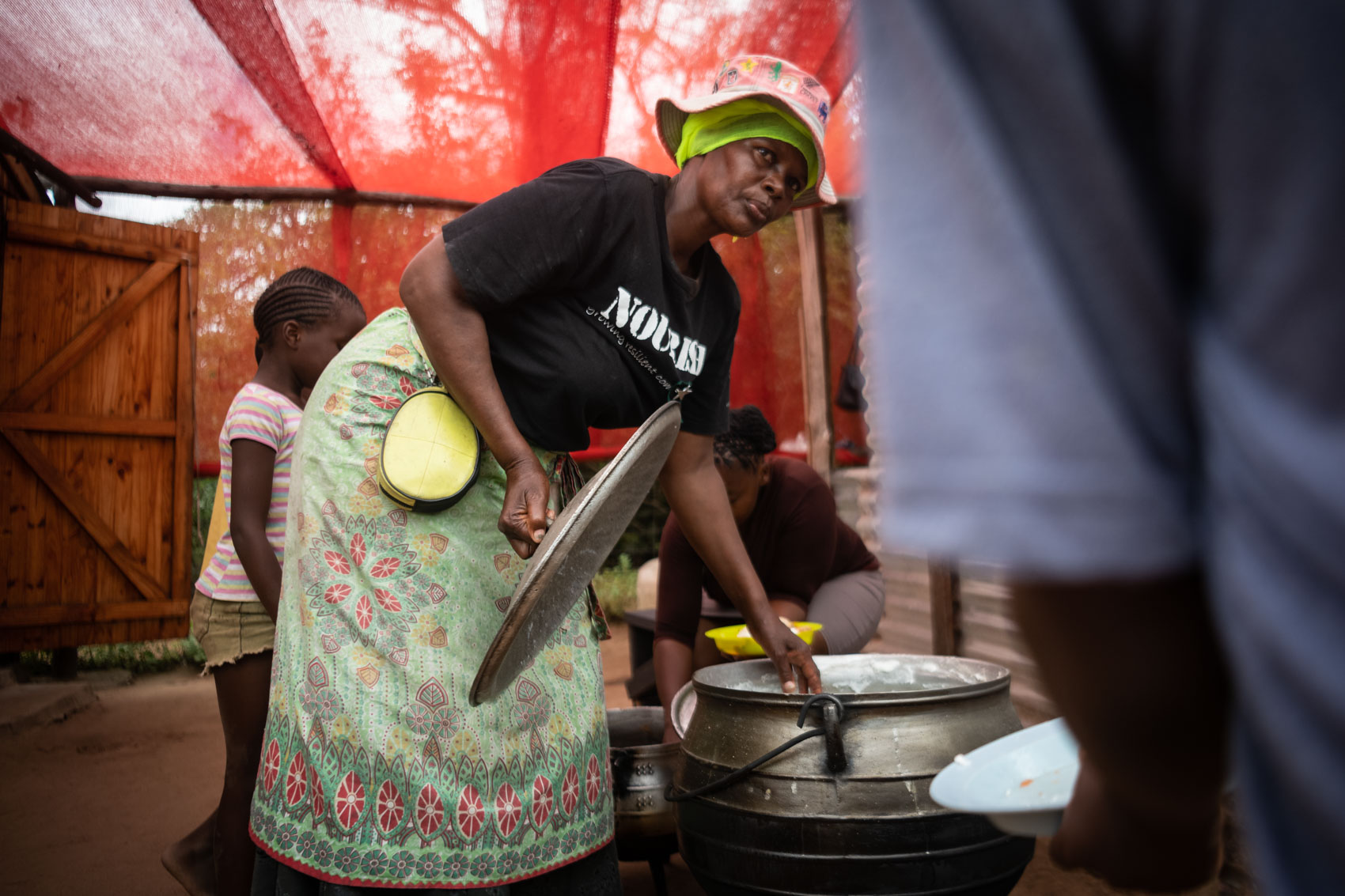 A granny worker at Nourish NPO opening the lid of a pot filled with porridge
